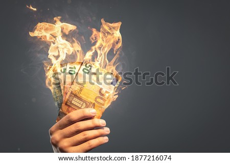 Burning Euro banknotes held by a hand Royalty-Free Stock Photo #1877216074