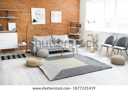 Stylish interior of living room with carpet and sofa Royalty-Free Stock Photo #1877231419