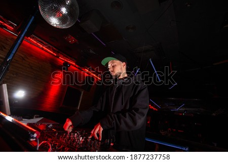 Confident DJ man mixing best track in nightclub at party. Nightlife concept. Disco ball. Professional music equipment. Dark backgroung with red lights. Royalty-Free Stock Photo #1877237758