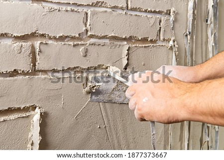 Professional Builder moulding decorative tile on wall from gips plaster . worker removing tape under plaster to imitate decorative brick on wall Royalty-Free Stock Photo #1877373667