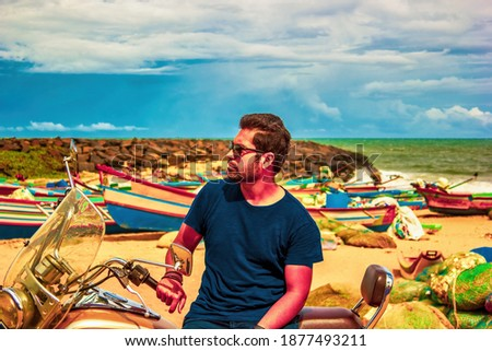An Indian ethnicity man with sunglasses, stubble and black hair sitting on a cruiser bike against seashore and cloudy blue sky. Side profile of a young south asian male Royalty-Free Stock Photo #1877493211