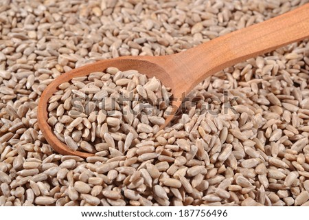 Cleared sunflower seeds in a wooden spoon #187756496