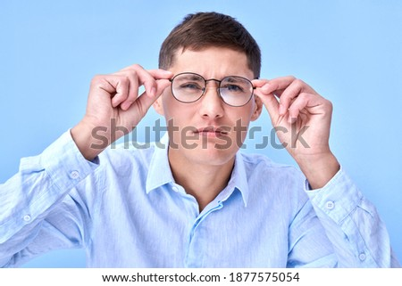 Studio shot caucasian man with poor eyesight holds hands on the rim of glasses and squints, trying to see something, looking at the camera isolated on blue background Royalty-Free Stock Photo #1877575054