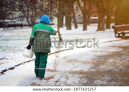 Worker spreading sand and salt to slipper road. Road treatment with de-icing mixturet, prevent slipping on road. Sprinkle salt on paving slabs to remove ice and prevent slipping accident Royalty-Free Stock Photo #1877621257