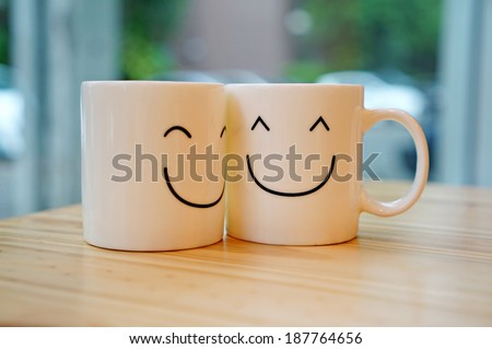 Two happy cups on wood table with black polka dot tablecloth. Concept about love and relationship #187764656