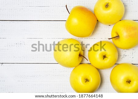 Heap of delicious yellow golden apples on white wooden table with copy space. Royalty-Free Stock Photo #1877664148