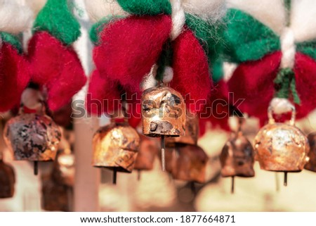 Selective focus view on bells with sheep wool bows in colors of Bulgarian flag. Traditional Bulgarian souvenirs Martenitsa on street fair. Handmade decorations for holidays - Christmas and Spring Day
