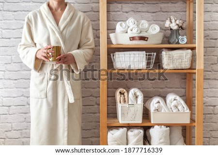 Woman in robe is standing and holding white wire basket of folded bed sheets near organized linen closet in bathroom. Sorted and folded towels in white wicker and wire baskets placed on wooden shelves Royalty-Free Stock Photo #1877716339