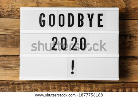 Lightbox with phrase Goodbye 2020! on wooden table, top view