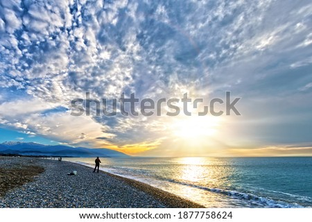 scenic sunrise landscape over sea shore at winter time with silhouette of fisherman and snow mountains on background. Wide view of sunset sky with clouds over ocean shore. People enjoying cloudscape Royalty-Free Stock Photo #1877758624