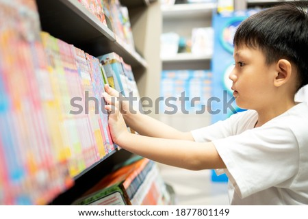 Asian little child selecting book while visiting bookshop,serious kid boy searching and looking for a fairy tale book in bookstore or choose a book from a bookshelf in a public library,reading concept Royalty-Free Stock Photo #1877801149