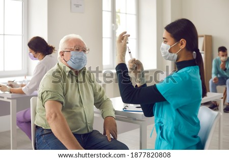 Antivirus vaccination for older people. Covid-19, pneumonia or flu preventive measures. Male senior citizen waiting to receive his vaccine. Asian doctor in face mask administering shot to mature man Royalty-Free Stock Photo #1877820808