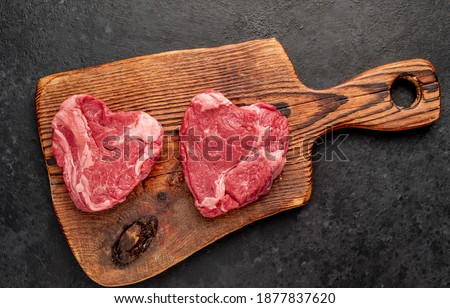 raw marbled beef steaks in the shape of a heart with spices on a stone background