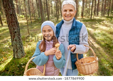 picking season, leisure and people concept - grandmother and granddaughter with baskets and mushrooms taking picture with selfie stick in forest