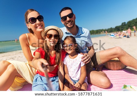 family, leisure and people concept - happy mother, father and two daughters having picnic on summer beach and taking picture with selfie stick