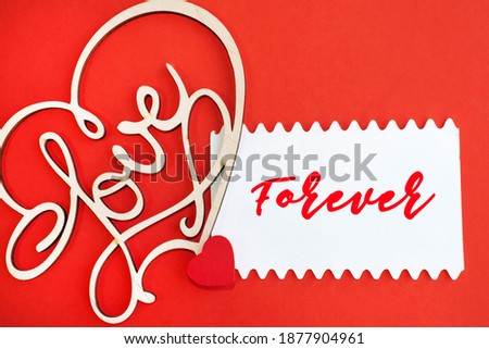 Forever is written on a white sheet that lies on a red background near a wooden heart with the inscription love. Valentine's Day