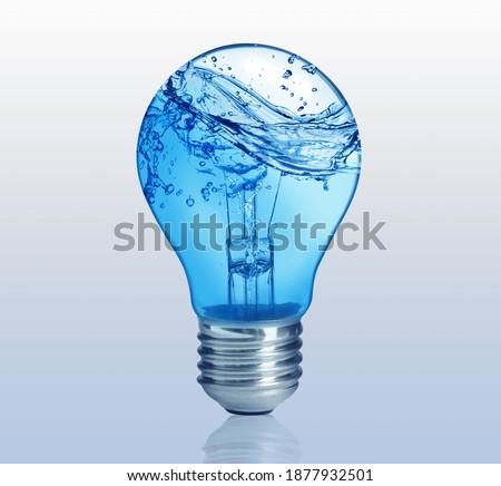 Light bulb with water splashes on light background. Alternative energy source