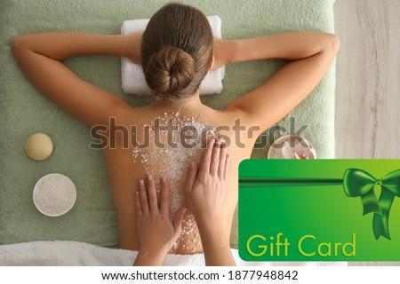 Spa salon gift card. Young woman having body scrubbing procedure