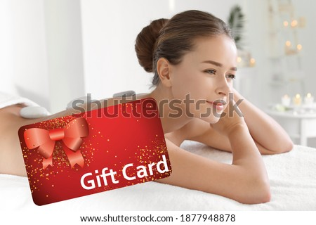 Spa salon gift card. Happy young woman having hot stone massage