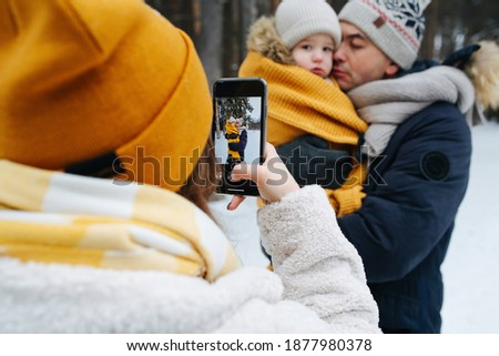 Mom taking winter picture of a dad with little daughter in hands. View from behind her shoulder. All wearing knit hats and scarves.