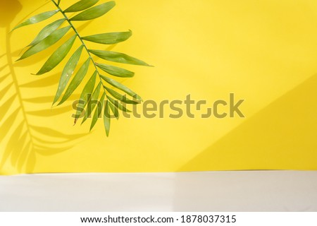 Minimal modern product display on ultimate gray and illuminating yellow background with palm leaves and shadow overlay