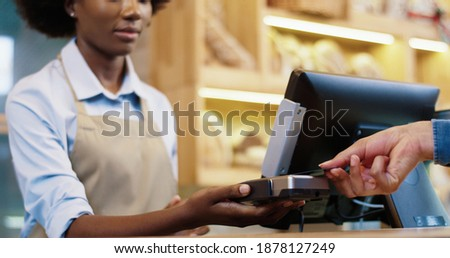Close up of African American female seller in mask and protective gloves selling food in bakery shop. Client hand paying with credit card on device. Small business. Shopping. Bakehouse concept