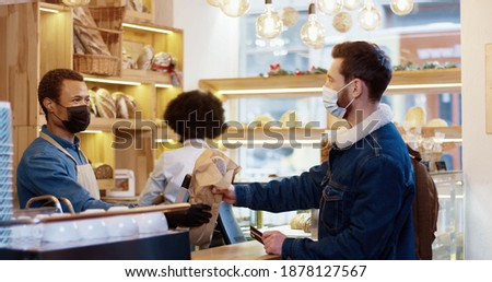 Side view of African American young man seller in mask and gloves selling fresh bread in bakery shop while female colleague working behind him. Male client paying with credit card in bakehouse