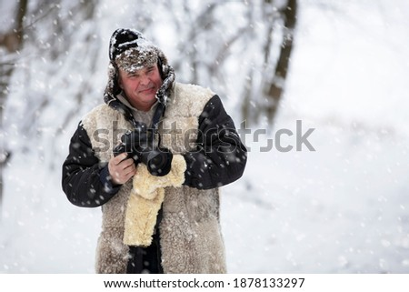 An elderly man in warm clothes takes pictures of nature in winter.