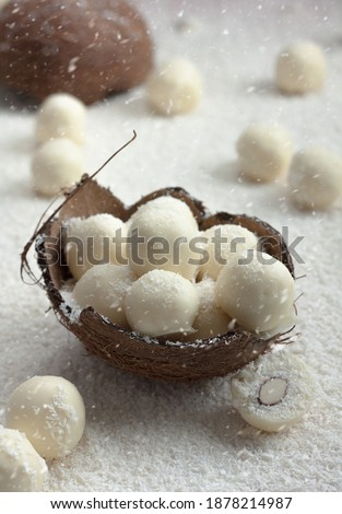 Homemade Raffaello balls, served in coconut shell over table covered with desiccated coconut, coconut snow, close up, winter food concept #1878214987