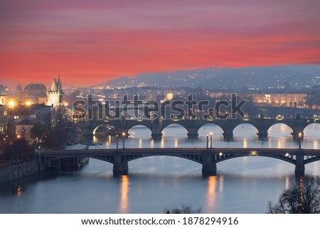 view of the Vltava river and the bridges on it between the bridges and the Charles Bridge and the surrounding architecture and light from the street lights in the center of Prague after sunset Royalty-Free Stock Photo #1878294916