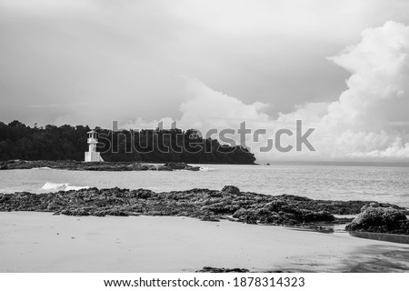 Black and white picture of sea shore with light house background.