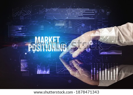 Businessman touching huge screen with MARKET POSITIONING inscription, cyber business concept Royalty-Free Stock Photo #1878471343
