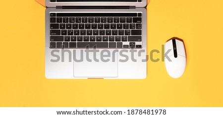 Horizontal flat lay minimalist photo with a silver grey laptop computer, and a wireless white-colored mouse on a yellow background. Royalty-Free Stock Photo #1878481978