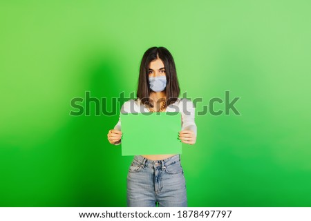 Serious girl in the surgical mask holding in hands green blank sheet isolated on the green background. Copy space for advertisement.