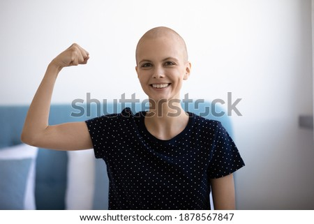 Own example. Portrait of strong willed female cancer patient having power to overcome disease. Self confident young woman combat against oncology looking at camera demonstrate muscles strength symbol Royalty-Free Stock Photo #1878567847
