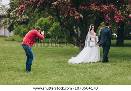 Professional wedding photographer in the process of photographing with the newlyweds in nature. Photography, concept. Royalty-Free Stock Photo #1878584170
