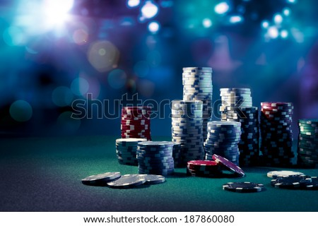 Poker Chips on a gaming table with dramatic lighting Royalty-Free Stock Photo #187860080