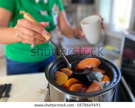Mulled wine being served from slow cooker by female in Christmas t shirt Royalty-Free Stock Photo #1878669691