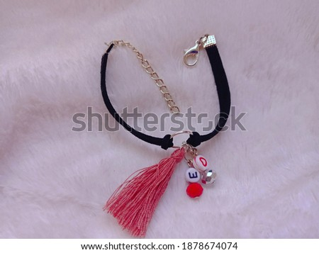 Photo of friendship bracelet with alphabet beads. Picture of thread bracelet with pink background