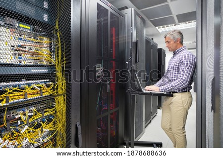 Technician Working on a Laptop In the secured data center Royalty-Free Stock Photo #1878688636