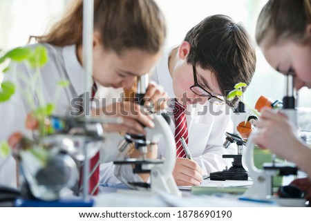 High school students making notes while conducting scientific experiment using microscopes in a biology class. Royalty-Free Stock Photo #1878690190