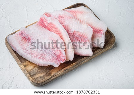Frozen fish fillet, on white background Royalty-Free Stock Photo #1878702331
