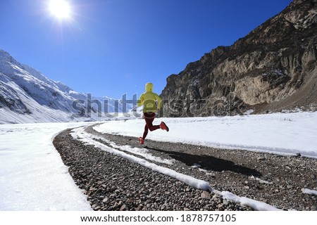 Woman trail runner cross country running in winter nature Royalty-Free Stock Photo #1878757105