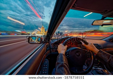 Movement of the car at night at high speed view from the interior with driver hands on wheel. Concept spped of life. Long exposure photo. Royalty-Free Stock Photo #1878758551