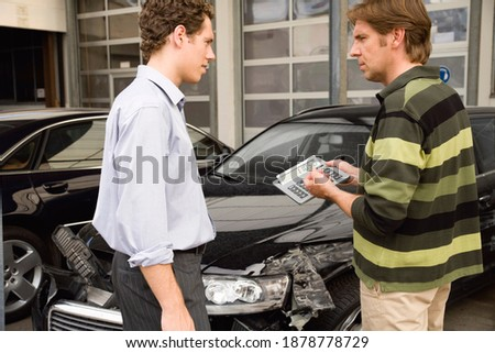 A claims adjuster showing the owner the settlement amount to be paid after assessing the damage done to a car. Royalty-Free Stock Photo #1878778729