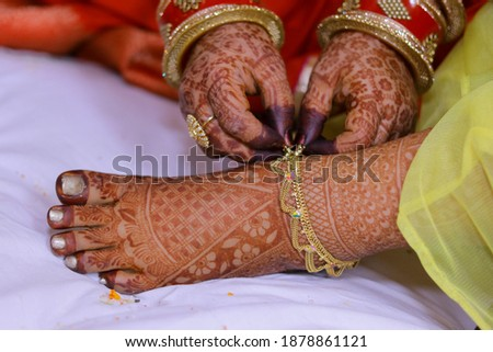 Picture of the bride foot which is decorated with mehndi . Indian bride getting her anklets on foot. Selective focus concept.