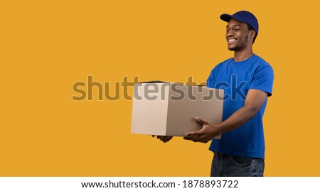 Portrait of cheerful african american delivery guy loader wearing blue cap and uniform holding cardboard container, giving it to the side, copy space, banner. Man isolated on orange studio background Royalty-Free Stock Photo #1878893722
