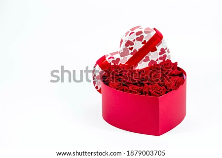 Valentine's Day. Red roses in a white box in the form of a heart on a white background. A gift for women on a holiday. The concept of delivering flowers. floristry and flower shops. Copy space.  Royalty-Free Stock Photo #1879003705