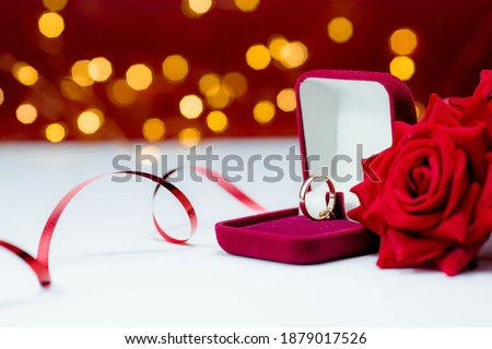 Banner. Gold ring, wedding ring in red box and , red rose on white-red background with beautiful bokeh. The moment of a wedding, anniversary, engagement, or Valentine's Day. Happy day. Royalty-Free Stock Photo #1879017526