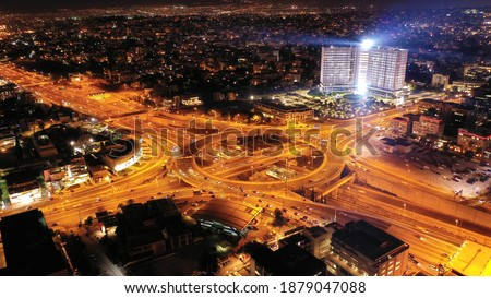 Aerial drone slow shutter night photo of illuminated urban elevated toll ring road junction and interchange overpass passing through Kifisias Avenue, Attica, Greece